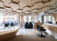 Sheets of plywood were layered to create the ceiling within this Parisian salon, which architect Joshua Florquin designed to represent natural environments