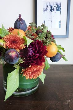 rusty orange mums, wine colored dahlias, figs, and tangerines with seeded fennel and other greenery