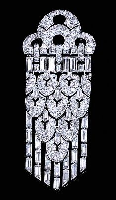A DIAMOND PENDENT BROOCH, BY LACLOCHE FRÉRES. Designed as circular-cut diamond tiered arches to the baguette-cut diamond links suspending a series of pierced pavé-set shield-shaped articulated panels with baguette-cut diamond detail and tassels, circa 1929, with French assay marks. Signed by Lacloche Frères, Paris, numbered.