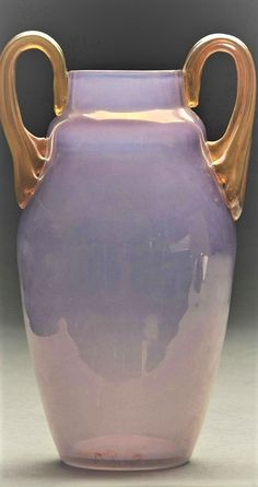 "Leotz vase in the Ausfuehrung genre has lilac translucent body with slight iridescence. The vase is finished with two applied reeded handles. Vase is 9-3/4"" to the top of the handles. Dimensions:9 -1/2"" x 6""."