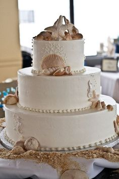 Beautiful beach wedding cake-gold/bronze shells. For the best officiant for your Outer Banks ceremony, or anywhere in NC, contact Rev. Dawn Marsh Gallogly, officiant4you.com/