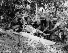 """Returning from an assault on Hill 717, men of Company """"L"""", 7th RCT, 3rd Infantry Division, help a wounded buddy onto a strecher for evacuation to an aid station.  3 July 1951.  Korea.  Signal Corps Photo #8A/FEC-51-23568 (Brigham)"""