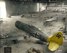 An American GI inspects a P-47 Thunderbolt, captured by German forces and studied in this hangar, Germany, April, 1945. In the foreground…