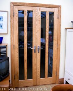 Tall glazed internal doors fitted into a new frame. This pair of double doors have been glazed with 4 tall clear glass panels. These doors and frame are made out of ash, which is a tough and very strong hardwood that has a lovely looking grain. The doors and frame have been stained with a light wood finish. Light stains like these look best when matched with a lighter furniture finish such as the satin chrome used here.