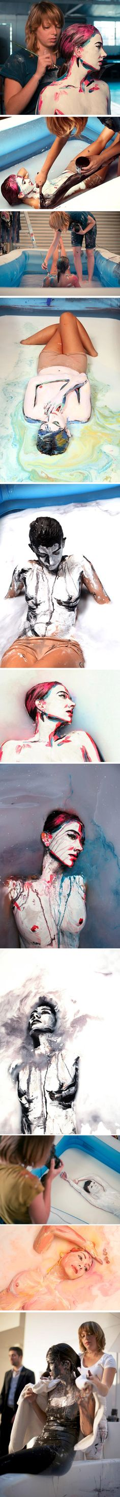 """Artists Alexa Meade and Sheila Vand have teamed up to create """"MILK: what will you make of me?"""" Alexa paints Sheila's portrait directly on top of her body before Sheila submerges in a pool of milk."""