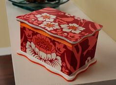 Make over a boring wood jewelry box with bright fabric and Mod Podge.