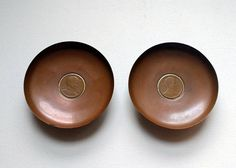 """Coin dishes pair of copper change dishes by Gallo Chile set with Chilean coins. Vintage copper coin dishes set with a central Chilean coin (probably 1 peso the face side not the value is shown) and the feet of the dishes are made from 20 centavos coins from the 1940s.  Stamped """"Gallo Chile"""" on the base with the rooster motif.  They are approximately 8½ cm, 3¾"""" in diameter. Condition: in good used vintage condition, there is some light scratching in line with their use as change dishes. I…"""
