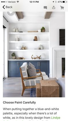 White floating shelves over blue built-in cabinets display fine pottery and decor in a cottage living room beside a white beveled fireplace.