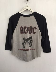 ACDC shirt 1981 vintage t shirt 80s band t-shirts vintage band raglan tee tshirt rock n roll tshirts concert tees heavy metal clothing small   Original 1981 ACDC For Those About To Rock tour raglan t shirt, front & back graphic, broken in soft and thin, graphic slightly faded   Label: n/a Tag size: Small Fits like: Small (XS in mens sizing) Chest: 16 Length: 23 Shoulders: n/a 50/50 Cotton/Poly