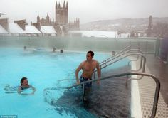 Letting off steam: Bathers enjoy the rooftop pool at the Thermae Bath Spa as snow continues to fall around them in Bath