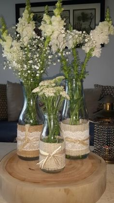 Idea sencilla y muy chic para centro de mesa. Botellas de vidrio adornadas con yute y  encaje, amarradas con cordón. Montadas sobre una base de tronco cortado.  Una combinación rústica y a la vez elegante.