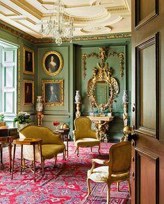 Gorgeous green walls, mustard upholstery, crimson rug--and gold leaf for daaaaaaaaays...