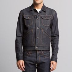 This raw denim jacket features a button up front, two breast pockets with flap…