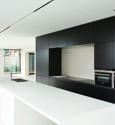 Dit 5 meter lange keukeneiland is naadloos vervaardigd uit pRAL, dit in combinatie met zwart gelakte muurkasten • Architect: Sofie Walravens (nieuwbouw • modern • keuken • zwartwit)