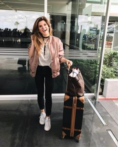 Grey t-shirt+black skinny jeans+white sneakers+blush satin bomber jacket+brown checked tote bag+black choker+black and camel suitcase. Spring Travel Outfit 2017