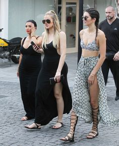 You can spot the similarities between the sisters' looks — from gladiator sandals to aviator shades to thigh-high slits.