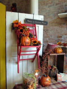 Fall display using a chair hanging on the door Paint chair red, with orange pumpkins and sunflowers