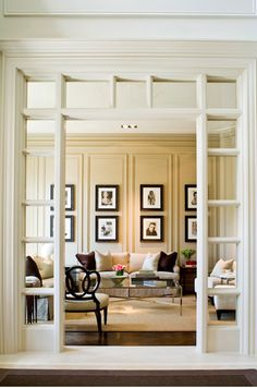 Beautiful cased opening with glass, framing a beautifully paneled living room.