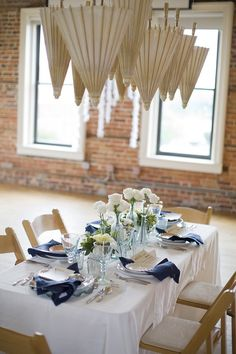 pretty tablescape with parasols.  would be cool if they were opened up and in colors.