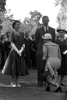 A young women curtsies to the Queen during a visit with the Duke of Edinburgh to the Unive...