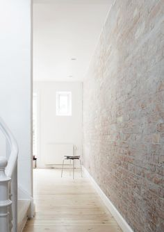Hallway with white-washed brick wall. ...