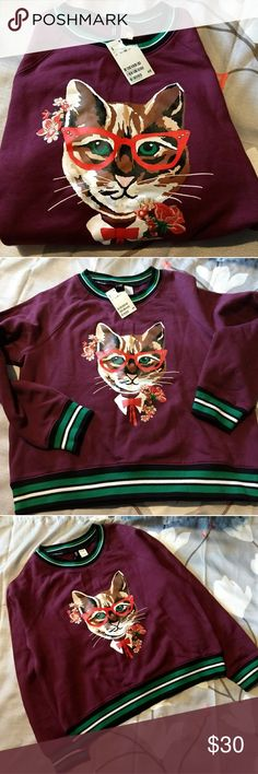 H & M burgundy sweatshirt Super cute long-sleeved burgundy colored sweatshirt with adorable kitten applique and embroidered flowers.  Green/black/white striped collar and cuffs  This was a gift for my daughter but she never wore it. Sales tag is still attached.  Cotton/polyester blend. Machine washable, line dry. Divided Tops Sweatshirts & Hoodies
