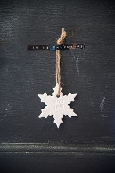 "ceramic snowflake hung with twine, with a ""it is christmas"" sticker."