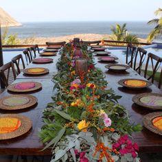 E o que falar dessa mesa comunitária que tanto suspiramos de amor? O caminho de mesa foi todo feito de flores, folhagens e muitas peças étnicas do nosso acervo. Os souplats de rattan ganharam cor (que tecido lindoooo) e essa vista??? #ohlindeza #conceptwedding #wedding #casamento #weddingdecor #decoracaodecasamento #decor #direcaodearte #identidadevisual #handmade #designfloral #floraldesign #arranjodeflores #flowers #flores #casamentodedia #casamentonapraia #casamentonojardim #natureza…