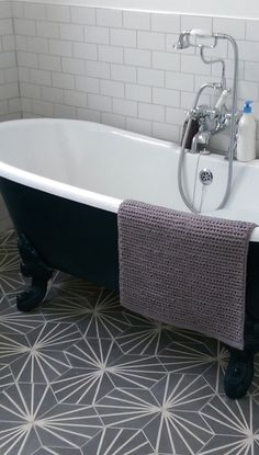 Our Hexagonal Graphic tile laid under a free-standing bath with metro wall…