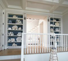Built-in bookcases with wallpaper display a beautiful collection of white and…