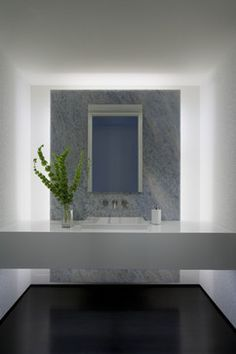 powder room floating wall covered in stone we have black fixtures, light wood counter, gray oak floors