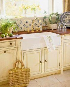 blue tiled back spash against white farm sink and beige cabinets.