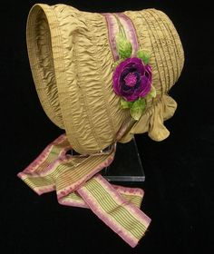 Bonnet: ca. 1840, English or American, silk tabby, reeds, buckram, trimmed with ribbons and velvet flower. [Search for Acc. No. 1996-362]