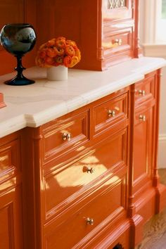The bright orange lacquer paint adds a fresh jolt of color and energy to the otherwise white and minimal space.