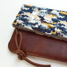 Beautiful leather fold over clutch bag constructed from chestnut vintage leather and premium printed cotton from the 'Bound' collection by April Rhodes.