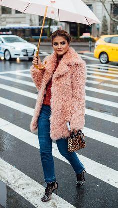 Thássia Naves usa camisa vermelha, casaco fluffy de pelos rosa, calça jeans reta, sandália de renda preta e bolsa Dior de onça