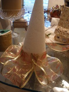 For this project you will need a styrofoam cone, the one I used was about 12 inches tall. Wire edged ribbon, and straight pins. I used two coordinating ribbons, and alternated the rows. Tied a bow to finish off the top. First I cut m...