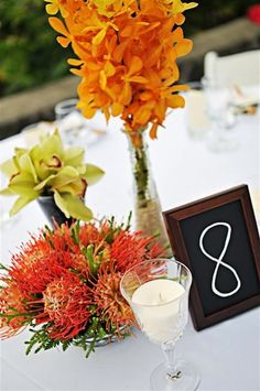 Chalkboard table numbers with flowers.  See more floral designs http://modernweddingshawaii.com/real-hawaii-wedding-holly-and-gabe/