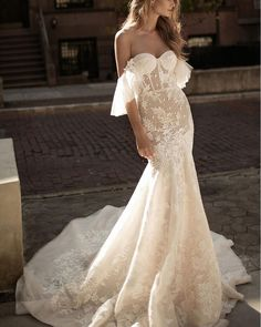 A masterful blend of structural and ethereal, this incredibly romantic mermaid gown features fluttery off-the-shoulder sleeves, sheer Swiss dots and gorgeous floral lace to contrast the molded cups and boned bodice. The curve-flaunting silhouette gives way to a dramatic cathedral train for an elegant finish.