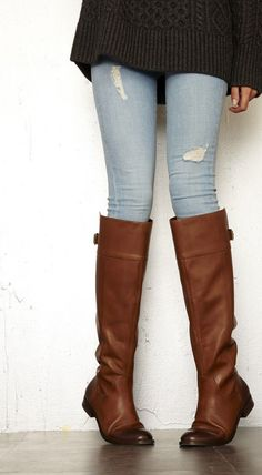 Luxurious leather riding boot with a back buckle detail and rounded toe.
