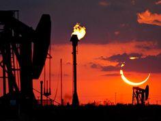 Un sol eclipsado se hunde hacia el horizonte de los pozos petroleros de Odessa, en Texas, el día domingo por la mañana. El eclipse duró aproximadamente 4 minutos y medio.