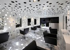 """The aluminum paneling gently obscured the landscape with a patterning of three types of round holes. In addition to allowing columns of light to pervade the space, these holes serve various practical functions of the salon including the fixtures for lights and hair dryers."""