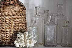old glass bottles, coral and vintage wicker 3 of my favourite things! Old Medicine Bottles, Old Glass Bottles, Bottles And Jars, Vibeke Design, Blue Interiors, Bottle Display, Apothecary Jars, Brighten Your Day, Natural Texture
