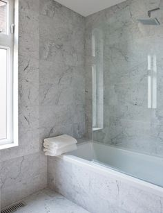 Achievable Marble Bathroom Carrara tiles mimic the look of marble slab. In this bathroom renovation, used standard Cararra marble 12 by 12 tiles, piecing them together to achieve a style very similar but much more affordable than a marble clad wall. Installing the tiles on the walls, floors, tub surround and window casing gives the space the high-end look of more expensive varieties of marble.