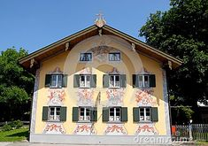 Photo made at Oberammergau in Bavaria (Germany). The picture shows the facade of a typical house of the small but beautiful country. The three-storey facade has two rows of four each and two small windows at the top. Windows with dark green (eight) and open the white fixtures are decorated with colored frames representing religious figures.