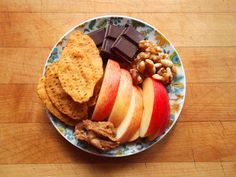 Sweet potato tortilla chips, a sliced gala apple with almond butter, and dark chocolate with walnuts.