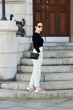 Shop this look for $165:  http://lookastic.com/women/looks/cropped-sweater-and-crossbody-bag-and-jumpsuit-and-gladiator-sandals-and-sunglasses/2772  — Black Cropped Sweater  — Black Leather Crossbody Bag  — White Jumpsuit  — White Leopard Gladiator Sandals  — Black Sunglasses