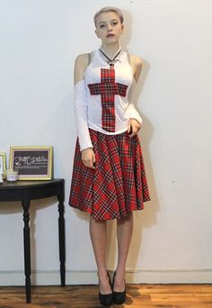 £12.00...80's punk top with red tartan cross/  This is a funky hand made vintage item by Pretty Disturbia, perfect to wear day or night. It can easily be dressed up or down!  FABRIC: Cotton   DETAIL: Well made and a great alternative design, It's a full length top with sleeves but cut out shoulders, shown in the pictures, Red tartan cross down the centre on the bodice. Great top to have will go with anything.  STYLING- Our PD stylists would wear this unique top with a midi skirt, leggings or…