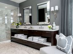 Fabulous bathroom with dark gray walls pairing with gray drapes. The bathroom features a dark brown standing open vanity with lower and upper drawers and a middle shelf holding fresh bath towels. The dual vanity pairs with a white counter and undermount sinks with gooseneck faucets. A pair of mirror framed mirrors hangs over the vanity flanked by a pair of two arm polished nickel sconces ... http://www.bathroom-paint.net/bathroom-paint-color.php