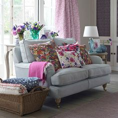 In this country living room a soft grey sofa is updated with piles of cushions in different shapes and sizes in gorgeous garden hues.